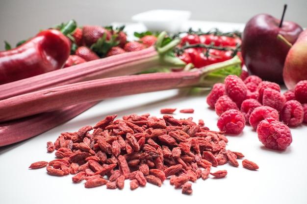 Goji e altri frutti rossi e verdure su uno sfondo bianco