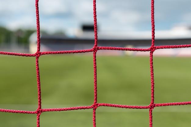 Gol di calcio allo stadio. sfondo del campo di calcio. colore delle reti bianche e rosse.