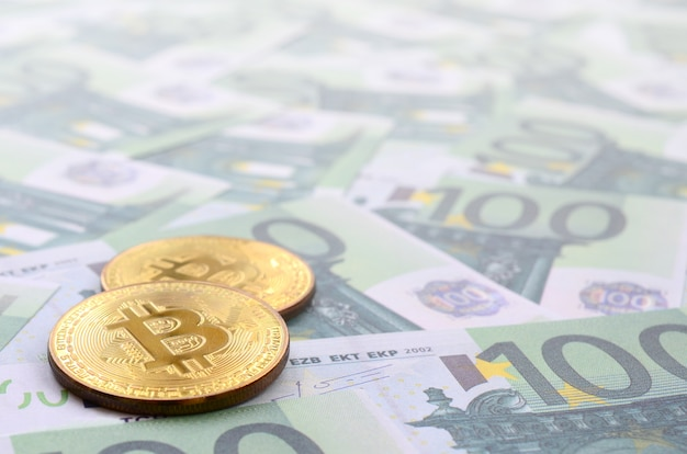 Golden bitcoin fisici sono bugie su un insieme di denominazioni monetarie verdi di 100 euro. un sacco di soldi formano un mucchio infinito