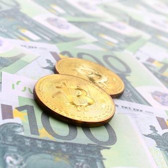 Golden bitcoin fisici sono bugie su un insieme di denominazioni monetarie verdi di 100 euro.