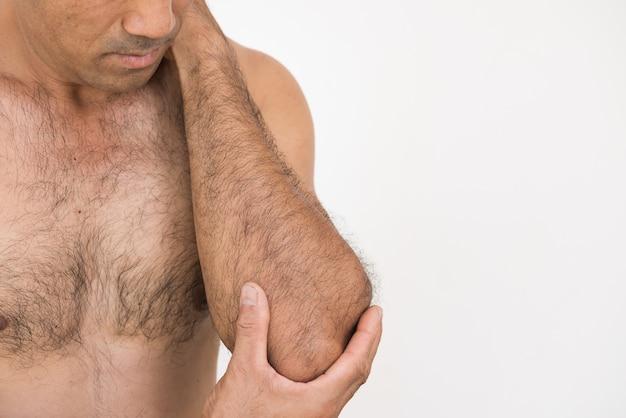 Gomito e dolore del braccio del primo piano e ferita del braccio su fondo bianco.