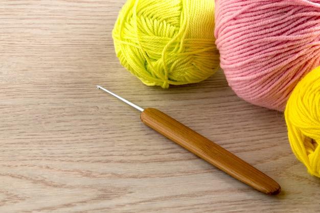 Gomitoli di lana, ferri da maglia, sul tavolo di legno