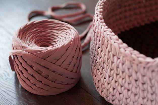 Gomitolo di lana lavorata a maglia rosa. lavoro a maglia filato rosa