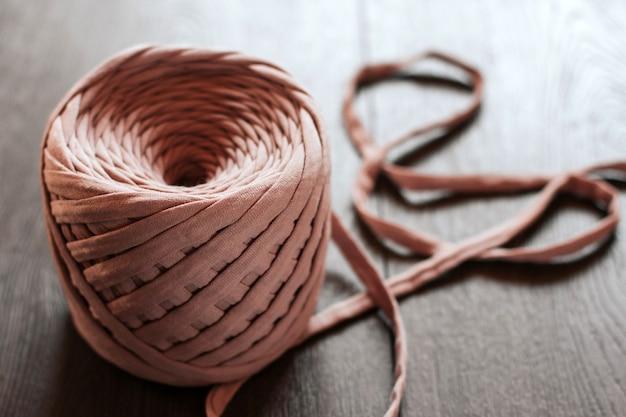 Gomitolo di lana lavorata a maglia rosa.
