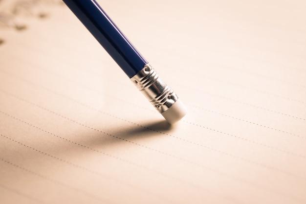 Gomma a matita che rimuove un errore scritto su un pezzo di carta, cancella, corregge e confonde il concetto.