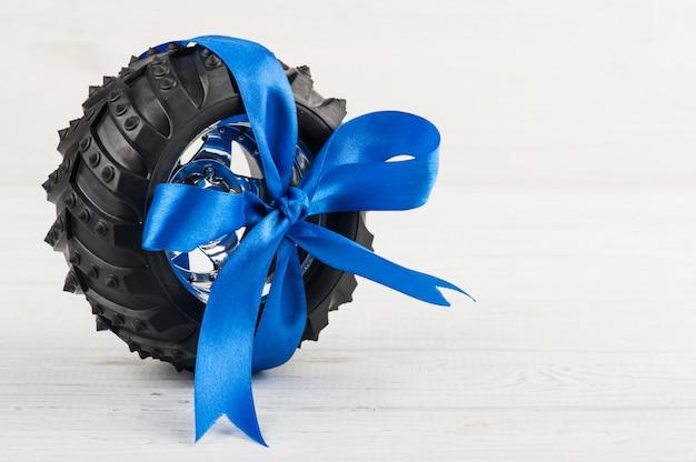Gomma del giocattolo dell'automobile legata con il nastro blu