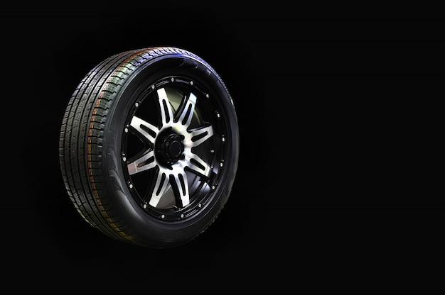 Gomma della ruota di automobile con l'orlo della lega isolato su fondo nero, spazio della copia