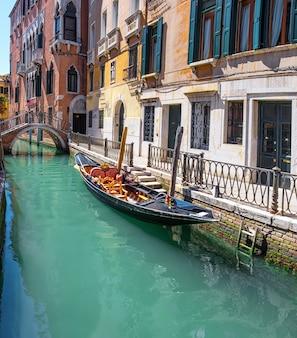 Gondola, vecchi edifici e ponte nel centro di venezia