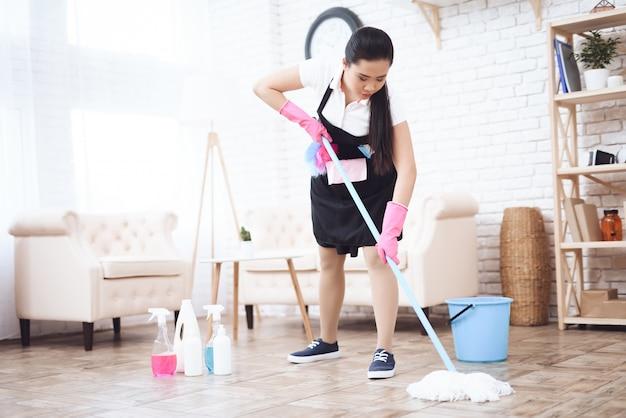 Governante che pulisce il pavimento con scopa e detersivi.