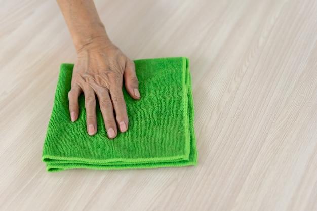 Governante con tessuto in microfibra strisciare sul pavimento di legno