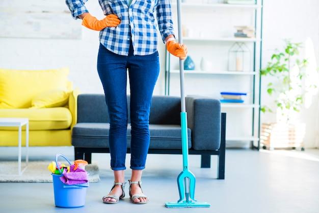 Governante femminile con attrezzature per la pulizia a casa