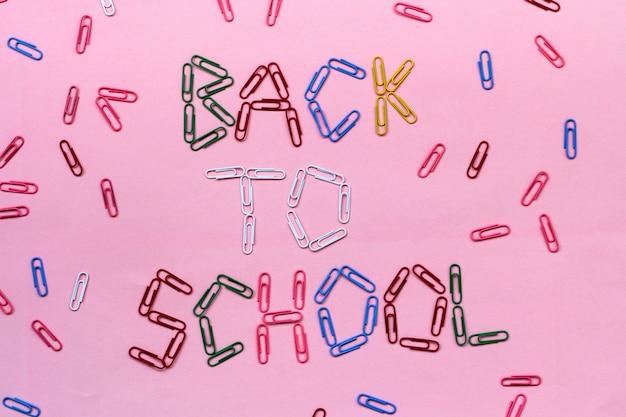 Graffette colorate su una rosa foderata con la scritta torna a scuola.