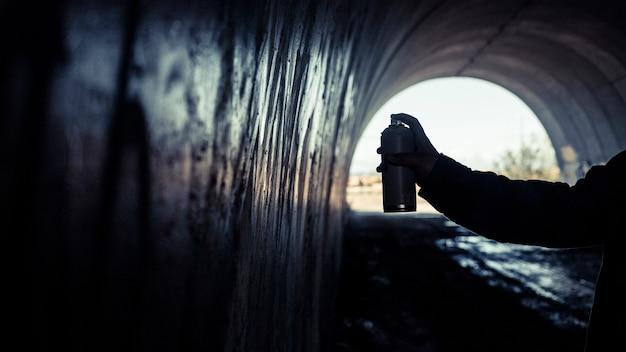Graffiti della pittura della mano dell'artista con la latta di spruzzo all'interno del tunnel
