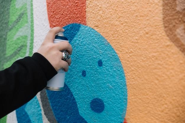 Graffiti della pittura della mano umana con la latta dell'aerosol