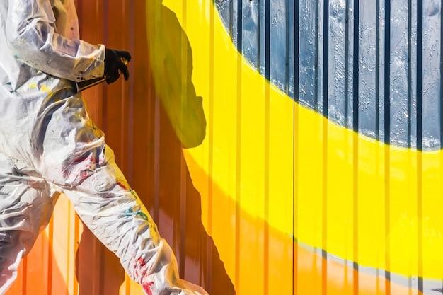 Graffiti sul muro e artista dei graffiti