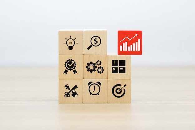 Grafica aziendale e di crescita icone su blocchi di legno.