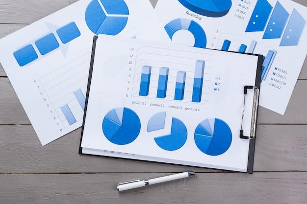 Grafici di carta finanziaria e grafici sul tavolo.