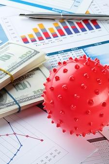 Grafici e istogrammi, banconote in dollari e coronavirus sulla scrivania