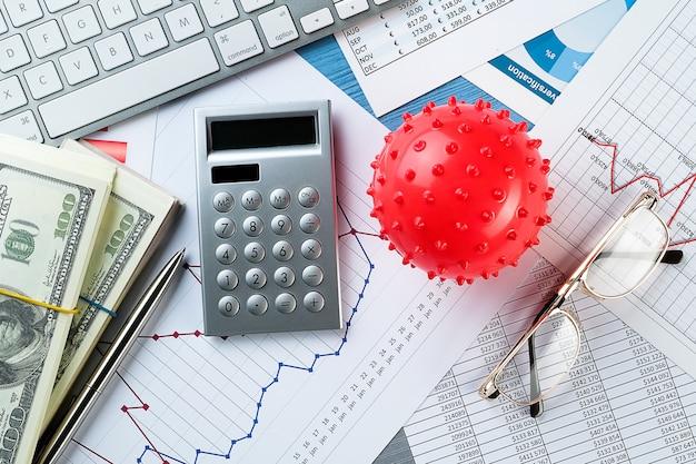 Grafici e istogrammi, coronavirus, denaro, calcolatrice sul tavolo. il declino dell'economia mondiale e del reddito.