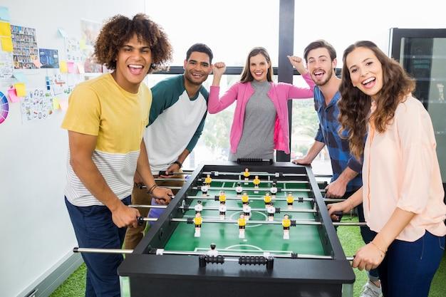 Grafici felici che giocano a calcio-balilla
