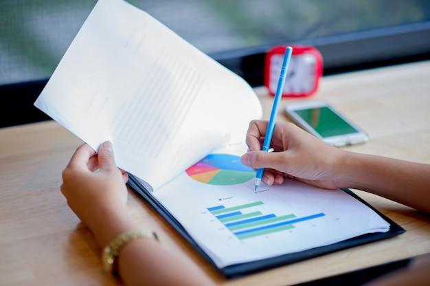 Grafico a mano e grafico analisi del grafico commerciale di imprenditori di successo