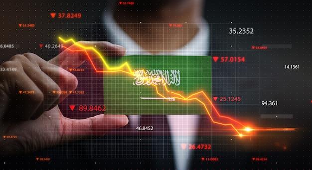 Grafico che cade davanti alla bandiera dell'arabia saudita. concetto di crisi