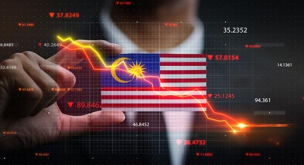 Grafico che cade davanti alla bandiera della malesia. concetto di crisi