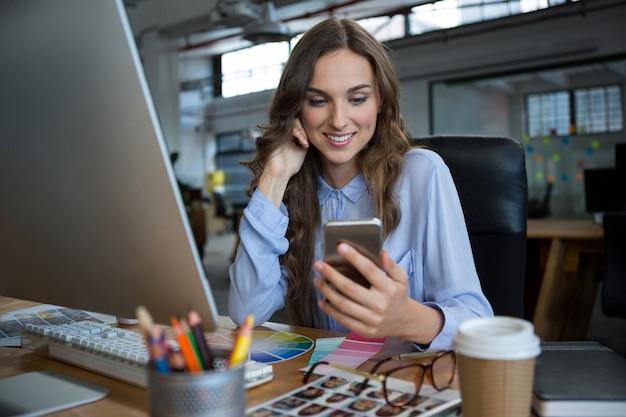 Grafico femminile che per mezzo del telefono cellulare allo scrittorio