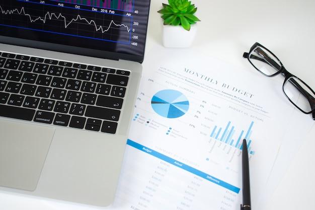 Grafico finanziario nel computer portatile sullo scrittorio moderno dell'impiegato di concetto.