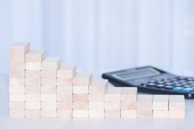 Grafico in calo da blocchi di legno con calcolatrice. concetto finanziario. copia spazio.