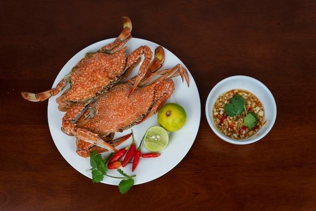 Granchi blu con la salsa di immersione dei frutti di mare tailandesi su un piatto, su un fondo di legno