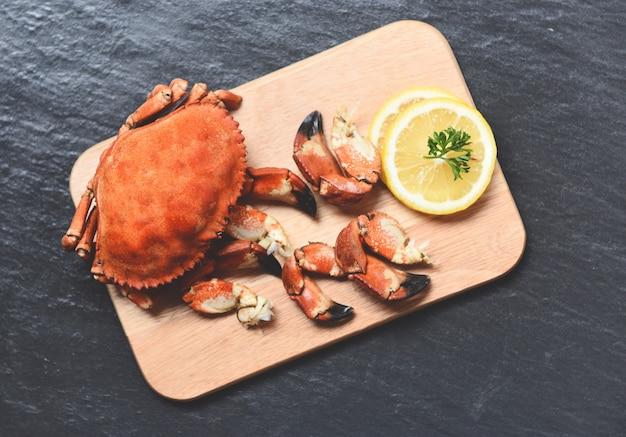 Granchi cucinati bolliti sul bordo di legno con il limone sul piatto nero servito frutti di mare chele di granchio di pietra rossa