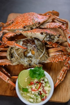 Granchio blu cotto a vapore sul piatto di legno con salsa di frutti di mare piccante, alimento tailandese