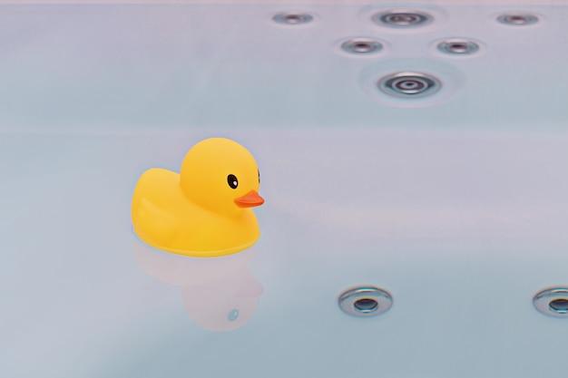 Grande anatra di gomma gialla che galleggia nella vasca da bagno