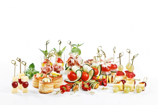 Grande attraente set di tartine con verdure, formaggio, frutta, bacche, salumi, frutti di mare, carne e decorazioni sul tavolo bianco