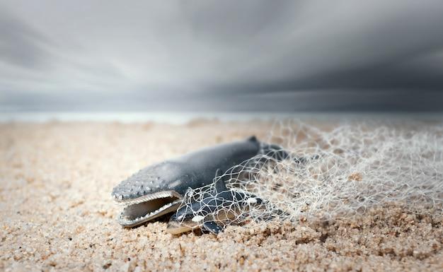 Grande balena e delfino aggrovigliato in una rete da pesca. ambientalismo e concetto di consapevolezza plastica