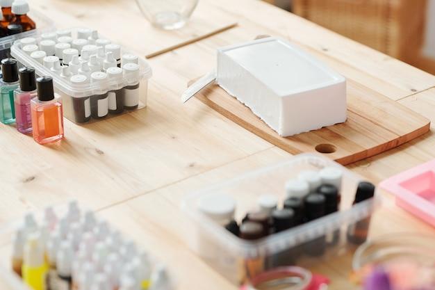 Grande barra di massa bianca di sapone duro su tavola di legno circondata da bottiglie con vari profumi e oli essenziali