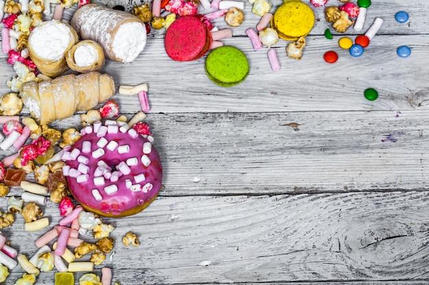 Grande bella scatola rosa con dolci sul tavolo di legno