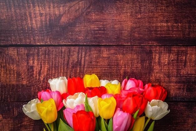 Grande bouquet luminoso di tulipani multicolori su assi di legno di colore marrone scuro.