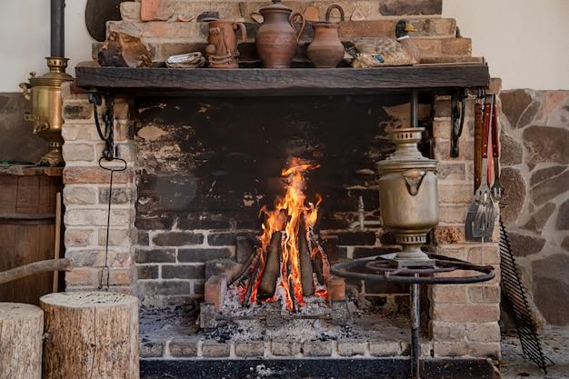 Grande camino con fuoco ardente e oggetti decorativi