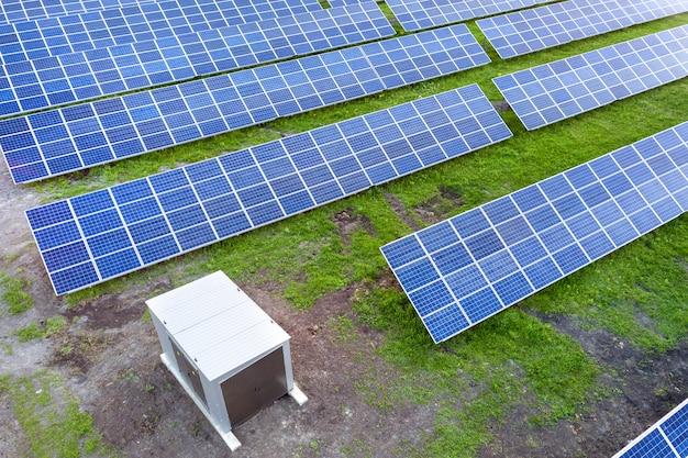 Grande campo del sistema fotovoltaico solare dei pannelli fotovoltaici che producono energia pulita rinnovabile sul fondo dell'erba verde.
