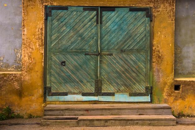 Grande cancello verde in legno per il magazzino. vecchio magazzino nel quartiere industriale.