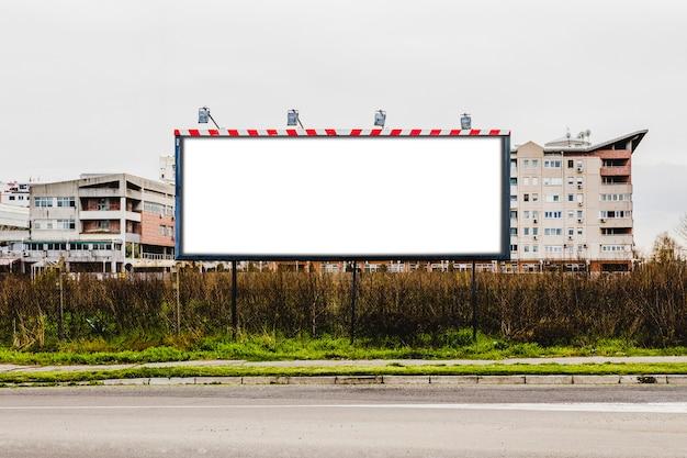 Grande cartellone di fronte all'edificio sul ciglio della strada