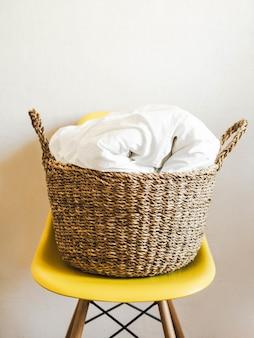 Grande cesto di vimini con coperta bianca su una sedia gialla