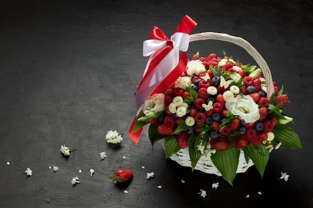 Grande cesto pieno di fragole, lamponi, mirtilli decorati con fiori bianchi su fondo nero