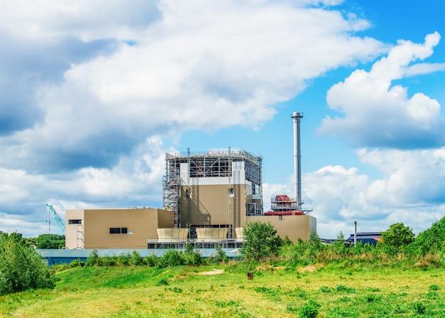 Grande fabbrica chiusa contro il cielo blu nuvoloso