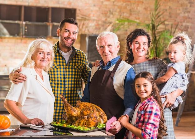 Grande famiglia in piedi vicino al prosciutto arrosto