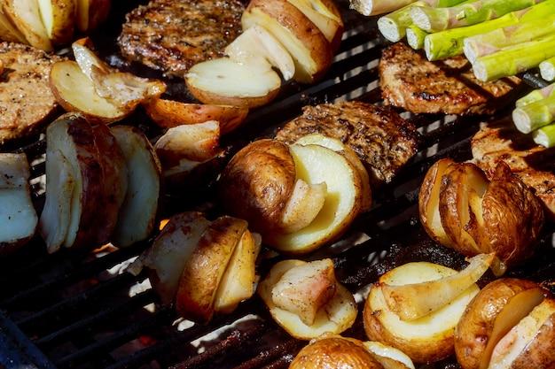 Grande fetta di patate in stile villaggio sulla griglia a carbone caldo per barbecue. fiamme di fuoco sullo sfondo.