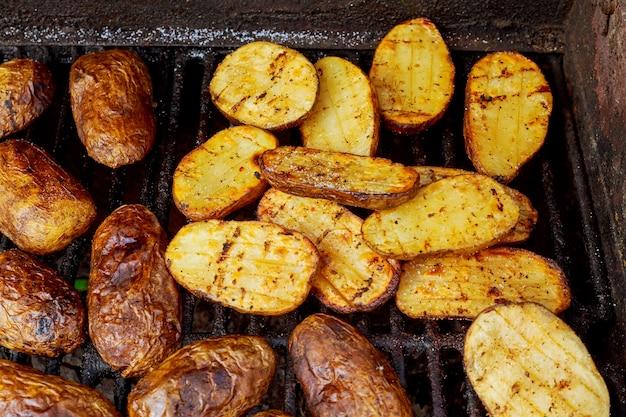 Grande fetta di patate in stile villaggio sulla griglia a carbone caldo per barbecue.