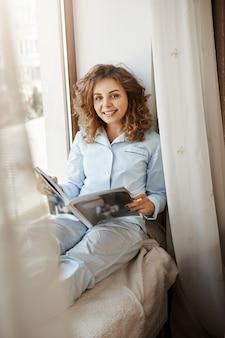 Grande giornata per saltare lavoro e doveri, pensando ai desideri personali. affascinante donna bionda dai capelli ricci in indumenti da notte carino, seduto sul davanzale della finestra sulla coperta, leggendo la rivista